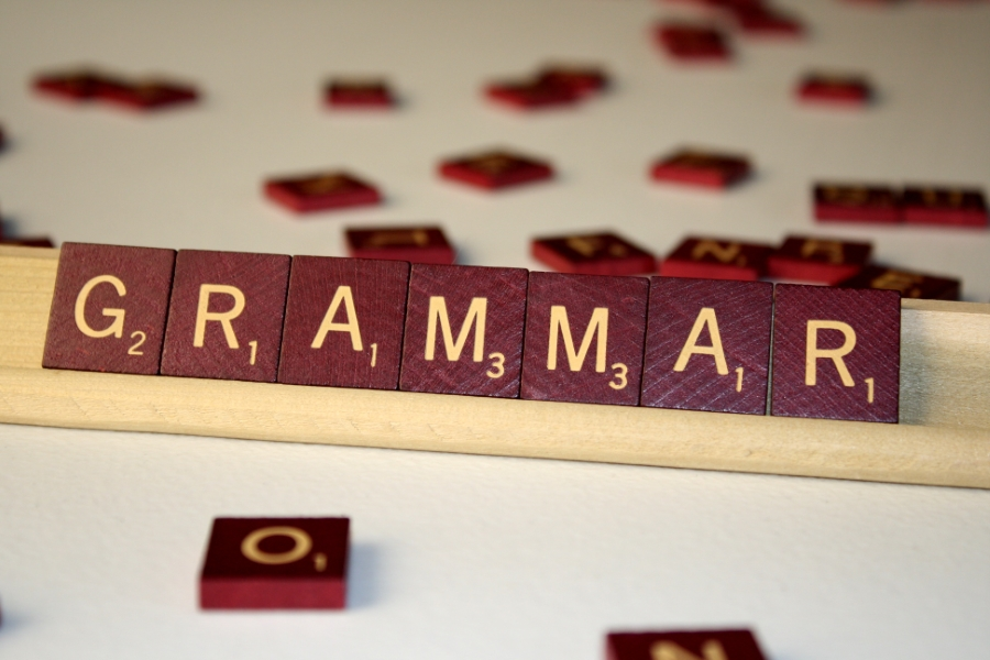 "Scrabble pieces with the word ""Grammar"" spelled out with tiles."
